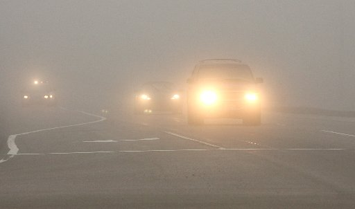 Cars with light on driving in Fog